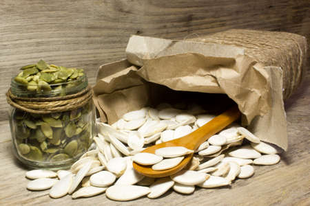 Pumpkin seeds and jar on wooden background Stock Photo