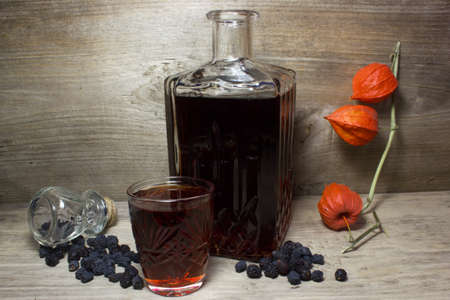 alcoholic beverage: Glass and carafe with red alcoholic beverage, dried black berries of the bird cherry. The wood background. Stock Photo