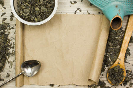 Sheet of parchment, green dry tea and kettle on wooden table Standard-Bild