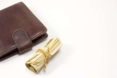 money roll: Wallet and a Roll of money tied with a rope on white background Stock Photo