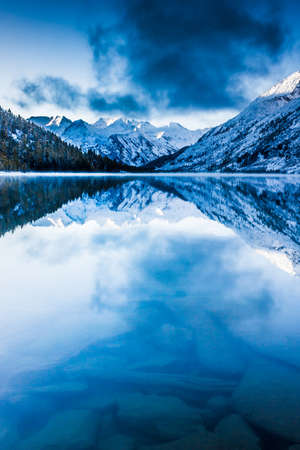 Beautiful blue lake in the mountains. Flat mirror surface of the water under the clouds. The beauty of winter nature. A tourist Trip through the nature reserve of Altai. Stock Photo