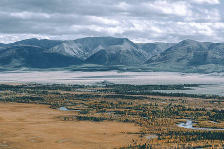 Beautiful mountain range under the clouds. Snowy peaks of rocks. View of mountain valley in Altai Republic.