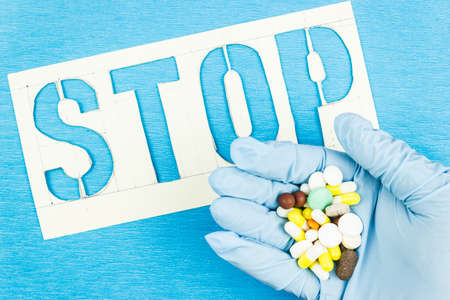 Hand in blue rubber glove with pills on the background of the blue table that says Stop. The danger of a drug overdose