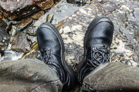 Black mountain boots in river. Footwear for tourist, hiking. Waterproof boots.