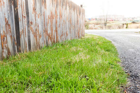 Green grass under wooden fence of old boards. Lawn in countryside, fenced land. Banque d'images - 121684180