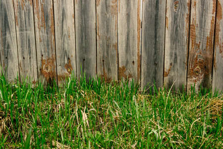 Green grass under wooden fence of old boards. Lawn in countryside, fenced land. Banque d'images - 121761183