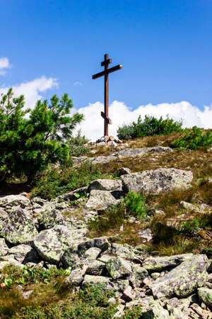 Orthodox wooden cross on mountain. Symbol of faith, pilgrimage to holy place.