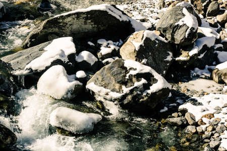 Mountain river in winter. Cold water flows among rocks. Journey onriver in mountains. 免版税图像