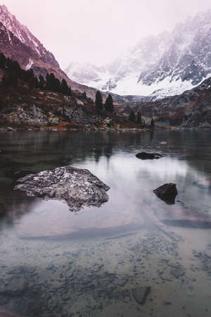Mountain lake in winter. Dawn in rocks. Travel in mountain valley along river