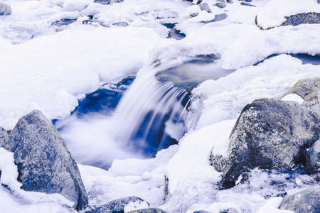 Mountain river with frozen water. Icicles by the river, cooling in nature. Winter weather in mountain valley Reklamní fotografie