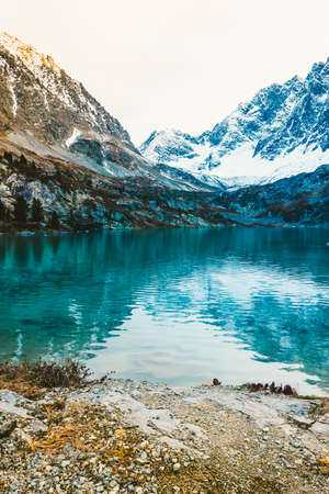 Mountain lake with rocks on horizon. Ridge with snow in valley of turquoise river
