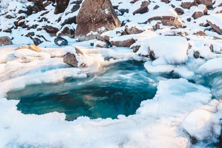 Winter mountain river under ice. Water froze and turned into icicles.