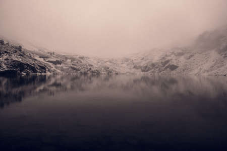 Mystical fog on mountain lake,  reflection of snowy ridge in water Imagens