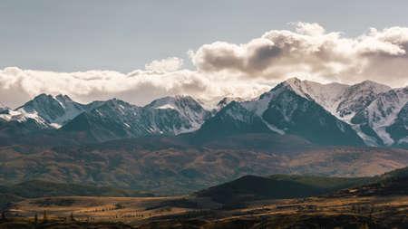 Valley with ridge of rocks on horizon. Snowy ridge of mountains under autumn sky
