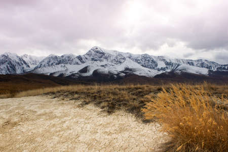 Dry cracked soil in mountain valley. Snowy mountain peaks on horizon. Autumn in steppe