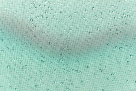 Raindrops or dew on tourist tent. Green cloth with drops as background
