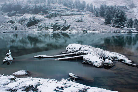 Snowy shore of mountain lake. Snowfall on river