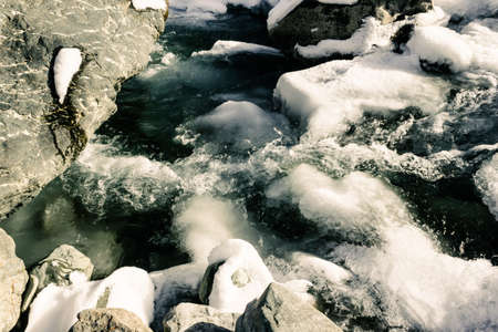 Mountain river in winter. Cold water flows among rocks. Journey onriver in mountains. Imagens