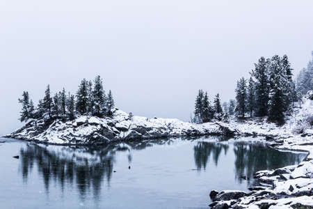 Winter lake, snow in coniferous forest on shore of mountain lake Imagens