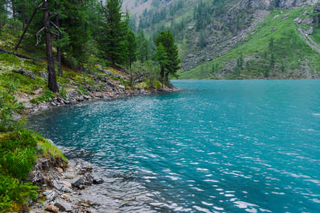 Rocky shore of blue lake. The surf of turquoise sea, waves come to shore