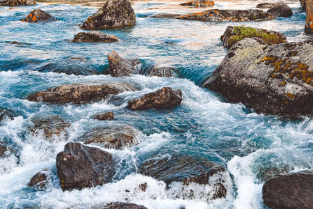 Rough river flow. The blue water of mountain river, the tide on sea with turquoise water and stone banks