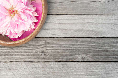 Peony flowers on wooden table. Pink petals for background Zdjęcie Seryjne