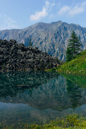 Mirror surface of mountain lake with reflection of stones and trees on shore Zdjęcie Seryjne