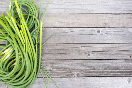 Green stalks of garlic on wooden table. The twisted stems of plants from seed. Preparation of summer salad for healthy diet