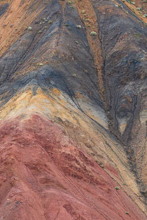 Colored hills, stripes of different colors on slope of canyon. Dry land due to lack of water. Drought in desert. Soil erosion