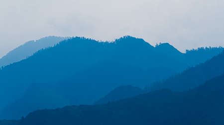 silhouettes of mountains in blue haze. Outline of gentle hills in the valley