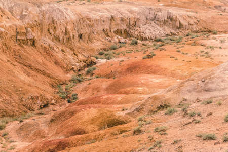 Red canyon in hills. Soil erosion following drought, climate change and formation of gullies. Lack of water in dry steppe