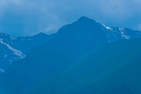 high cliffs in blue haze, silhouette of mountain range in fog, meditation and relaxation in nature