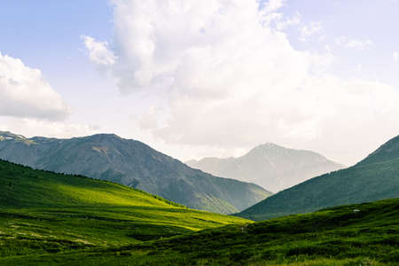 rocky ridge on horizon in mountain valley, green slopes of gentle hills, beauty of nature for relaxation and meditation Stock fotó