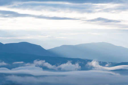 clouds and rays of dawn in mountain valley, soft light in early morning, meditation in nature. Gentle hills in bluish haze, silhouettes of mountains