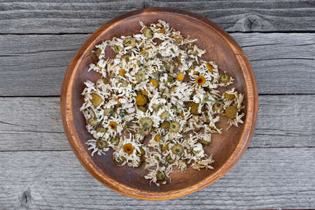 dry chamomile blossoms on wooden table, cooking green healing tea