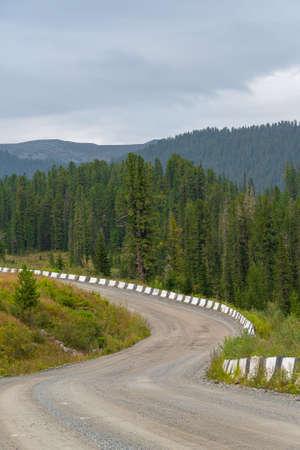 bend dirt mountain road with stone safety barrier