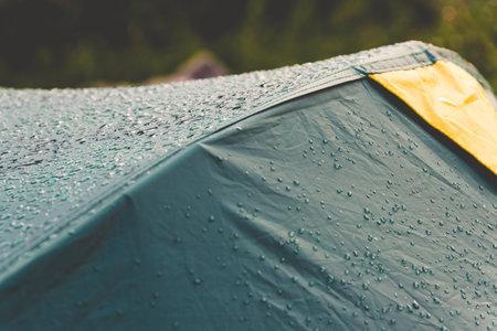 Dew drops on green tourist tent. Waterproof fabric rain, test of bad weather