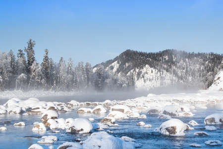 Boulders in cold water are covered with snow. Winter river on frosty morning.