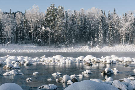 Winter landscape of lake with misty surface. Rocks and trees on river bank are covered with snow.