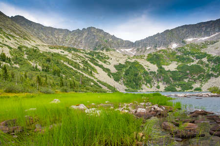 Lake at foot of mountain range. River in mountain valley along rocks. Summer morning in mountains of Siberia