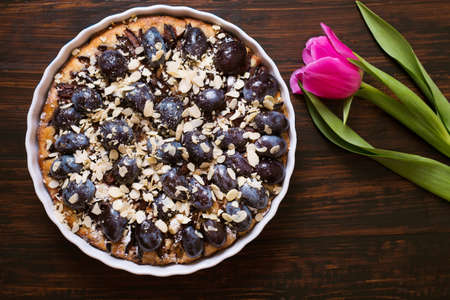 pie with plums on a dark wooden background, tulips