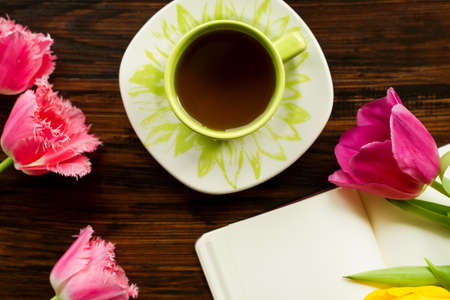todo list: Breakfast. A cup of tea, flowers, notes on the wooden background Stock Photo
