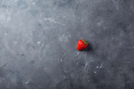 loosely: Strawberry. Fresh strawberry on dark background . Red strawberry. Loosely laid strawberries in different positions. Copyspace.