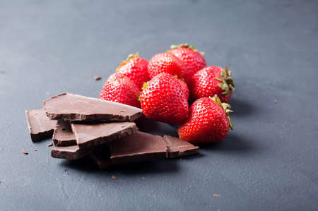 Strawberry with slices of chocolate on a dark background