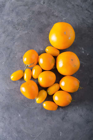 Tomatoes of different varieties. Colorful tomatoes Tomatoes background. Fresh tomatoes Healthy food concept. Colorful festive still life. Loosely laid tomatoes in different positions. Yellow tomatoes Stock Photo