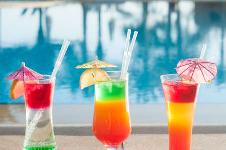 Colored cocktails on a background of water. Colorful cocktails near the pool. Beach party. Summer drinks. Exotic drinks. Glasses of cocktails on table near pool. Summer drinks photo concept. ?ocktail