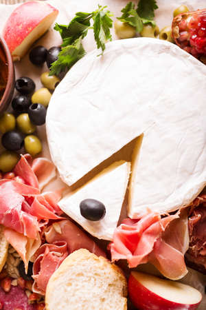 carnes y verduras: Típico tradicional española salmón ahumado y jamon servido en tabla de corte rústico con queso en rodajas de brie, tomate y aceitunas en tabla de cortar de madera rústica sobre fondo rústico, vista superior Foto de archivo