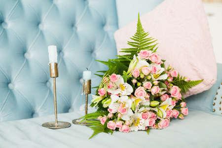 blue velvet: Bridal bouquet. Bridal bouquet on a blue velvet sofa. Candles. Wedding photo concept. Summer wedding. Sensual Wedding Photo. Roses Stock Photo