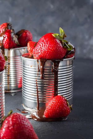 conservative: Fresh strawberry on gray background . Dessert with strawberries and chocolate, caramel. Strawberries in the iron pot. Copyspace. Stock Photo