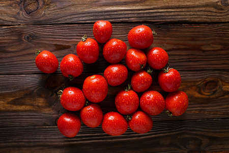 loosely: Red tomatoes with water drops. Tomatoes of different varieties. omatoes background. Fresh tomatoes Healthy food concept. Colorful festive still life. Loosely laid tomatoes in different positions. Stock Photo